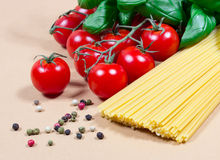 Raw pasta and ingredients for pasta with tomatoes and basil. Raw pasta and ingredients for pasta with tomatoes, basil and pepper Stock Image