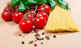 Raw pasta and ingredients for pasta with tomatoes and basil. Raw pasta and ingredients for pasta with tomatoes, basil and pepper Stock Photos