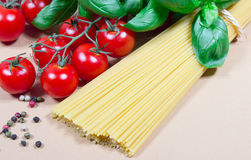 Raw pasta and ingredients for pasta with tomatoes and basil. Raw pasta and ingredients for pasta with tomatoes, basil and pepper Royalty Free Stock Photo