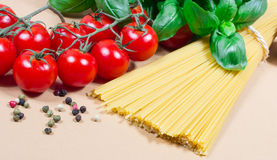 Raw pasta and ingredients for pasta with tomatoes and basil. Raw pasta and ingredients for pasta with tomatoes, basil and pepper Royalty Free Stock Photos
