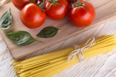Raw pasta and ingredients with tomatoes, basil. Stock Photos