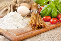 Raw pasta  and ingredients on the wooden board Royalty Free Stock Photography