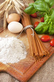 Raw pasta  and ingredients on the wooden board Royalty Free Stock Photo