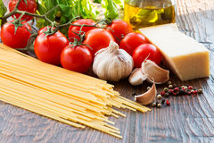 Raw pasta ingridients. Raw pasta, tomatoes and spices Stock Photography