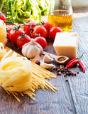 Raw pasta ingridients. Raw pasta, tomatoes and spices Royalty Free Stock Photography