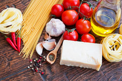 Raw pasta ingridients. Raw pasta, tomatoes and spices Stock Images