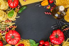 Raw pasta with ingridients on black board Royalty Free Stock Images