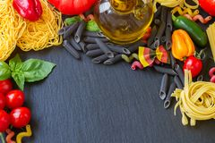 Raw pasta with ingridients on black board Stock Image