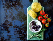 Raw pasta. Italian rustic culinary background, raw pasta with olives and tomatoes, top view Stock Photography