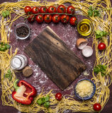 Raw pasta, lined frame around ingredients border ,place for text on wooden rustic background top view Stock Images