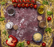 Raw pasta, lined frame around ingredients, grated cheese, peppers, pepper, salt on wooden rustic background top view stock image