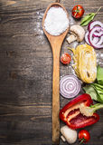 Raw pasta with mushrooms, peppers, basil and chives and vintage wooden spoon on wooden rustic background top view close up border, Royalty Free Stock Photography