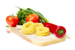 Raw pasta nest and ingredients for tomato sauce Royalty Free Stock Images