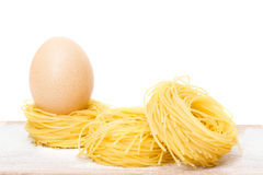 Raw pasta nests and egg Royalty Free Stock Photos