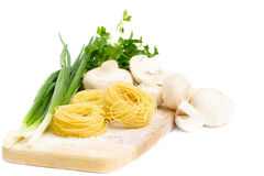 Raw pasta nests and ingredients for mushroom sauce Stock Photo