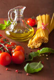 Raw pasta olive oil tomatoes. italian cooking in rustic kitchen Stock Images