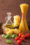 Raw pasta olive oil tomatoes. italian cooking in rustic kitchen Royalty Free Stock Photography