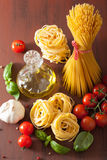 Raw pasta olive oil tomatoes. italian cooking in rustic kitchen Stock Image