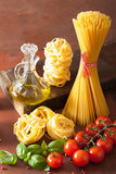 Raw pasta olive oil tomatoes. italian cooking in rustic kitchen Stock Photo