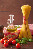Raw pasta olive oil tomatoes. italian cuisine in rustic kitchen Royalty Free Stock Photos