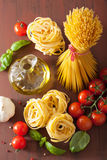 Raw pasta olive oil tomatoes. italian cuisine in rustic kitchen Stock Image