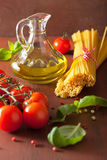 Raw pasta olive oil tomatoes. italian cuisine in rustic kitchen Stock Photography