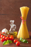 Raw pasta olive oil tomatoes. italian cuisine in rustic kitchen Stock Photos
