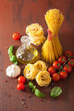 Raw pasta olive oil tomatoes. italian cuisine in rustic kitchen Royalty Free Stock Image