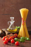Raw pasta olive oil tomatoes. italian cuisine in rustic kitchen Stock Photo