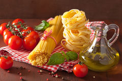 Raw pasta olive oil tomatoes. italian cuisine in rustic kitchen Royalty Free Stock Photography