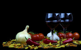 Raw pasta, peppers, red wine, glasses, onion Stock Images