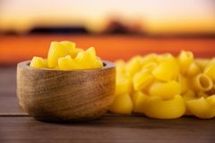 Raw pasta pipe rigate with autumn field behind stock photography