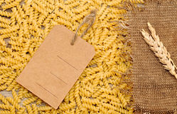Raw pasta, price and wheat ears with tag Royalty Free Stock Photo