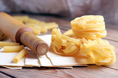 Raw pasta with rolling pin on a table Stock Images