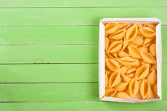 Raw pasta shells on a green wooden background with copy space for your text. Top view Royalty Free Stock Images