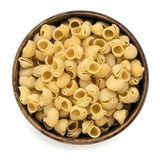 Raw Pasta Shells in Wooden Bowl Top View Isolated. Raw pasta shells in wooden bowl, top view, isolated on white Stock Photos