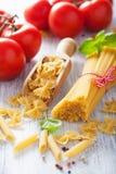 Raw pasta spaghetti farfalle penne, tomatoes. italian cuisine Stock Photos