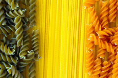 Raw Pasta Spaghetti and Fusilli. Raw pasta arrangement with spaghetti and red and green fusilli Royalty Free Stock Photo