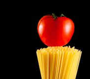 Raw pasta spaghetti with tomato on top on black background with space for text Royalty Free Stock Photos