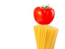 Raw pasta spaghetti with tomato on top on white ba Royalty Free Stock Images