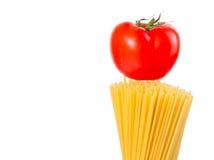 Raw pasta spaghetti with tomato on top on white ba Royalty Free Stock Images