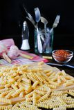 Raw pasta, spices, salt shaker, garlic, knife and fork in a glass jar or stand, lie on a dark wooden table. The concept of Italian stock image