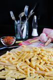 Raw pasta, spices, salt shaker, garlic, knife and fork in a glass jar or stand, lie on a dark wooden table. The concept of Italian stock photos