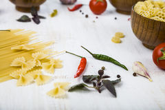 Raw pasta and spices in wooden table. Pasta and ingredients: chi Royalty Free Stock Photo