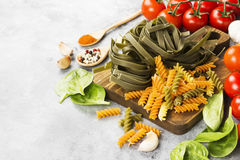 Raw pasta of tagliatelle with spinach and fusilli pasta with spi. Nach and tomatoes, and ingredients for cooking cherry tomatoes, spices, garlic, spinach leaves Royalty Free Stock Images