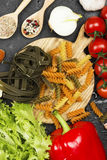 Raw pasta of tagliatelle with spinach and fusilli pasta with spi. Nach and tomatoes, and ingredients for cooking cherry tomatoes, spices, garlic, spinach leaves Royalty Free Stock Photo