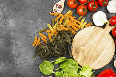 Raw pasta of tagliatelle with spinach and fusilli pasta with spi. Nach and tomatoes, and ingredients for cooking cherry tomatoes, spices, garlic, spinach leaves Stock Photos