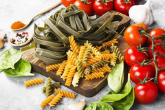 Raw pasta of tagliatelle with spinach and fusilli pasta with spi. Nach and tomatoes, and ingredients for cooking cherry tomatoes, spices, garlic, spinach leaves Royalty Free Stock Photos