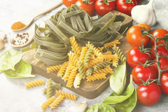 Raw pasta of tagliatelle with spinach and fusilli pasta with spi. Nach and tomatoes, and ingredients for cooking cherry tomatoes, spices, garlic, spinach leaves Stock Photo