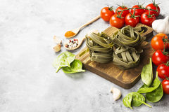 Raw pasta of tagliatelle with spinach and ingredients for cookin. G cherry tomatoes, spices, garlic, spinach leaves on a light background. Copy space. Food Stock Images